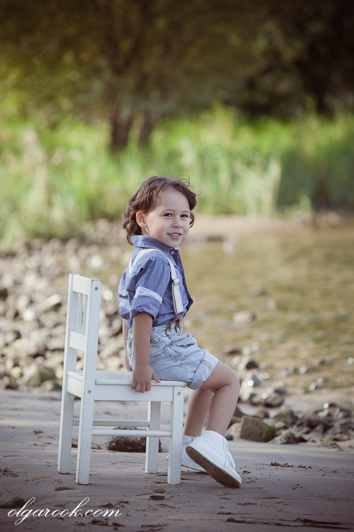 A romantic and dreamy child portrait depicting a little boy sitting on a small chair at a river bank