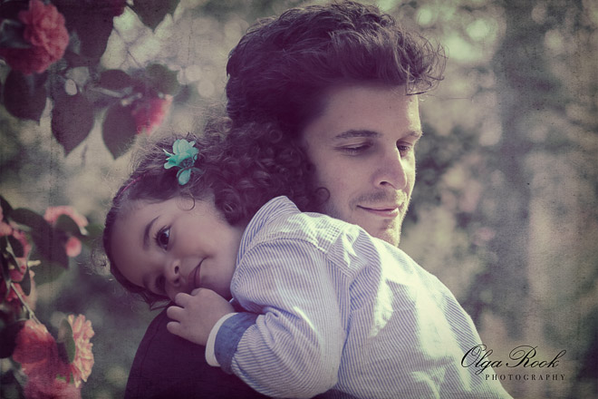 Emotional artistic portrait of a little girl on her father's shoulder. Their soft smiles show their trust and deep emotional connection