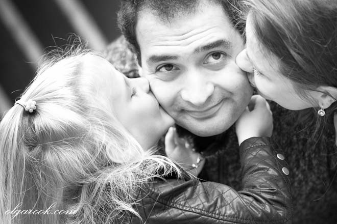 emotional portrait of a happy father kissed by his daughters on his both cheeks