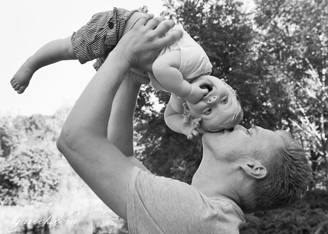 Photo of a father holding his little son in the air and kissing him on his head.
