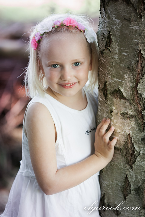 Romantic portrait of a blond little girl standing next to a tree