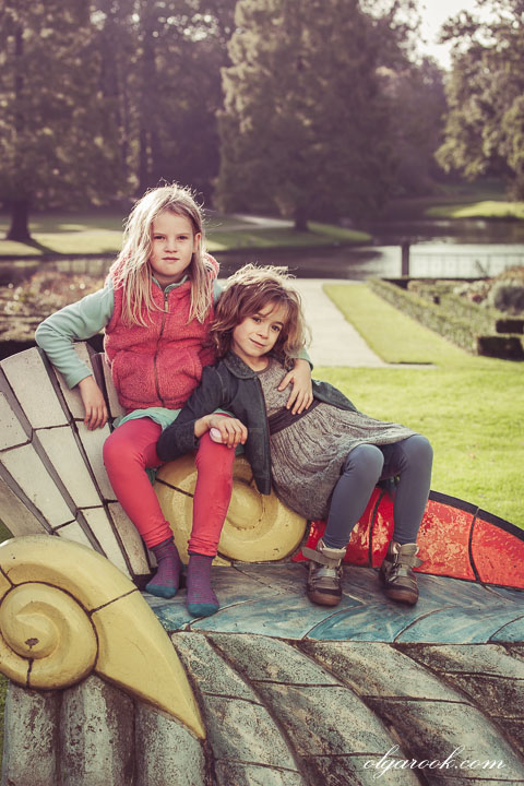 Portrait of two little girls posing in a park: one girl has a dominant look, another girl looks dreamy