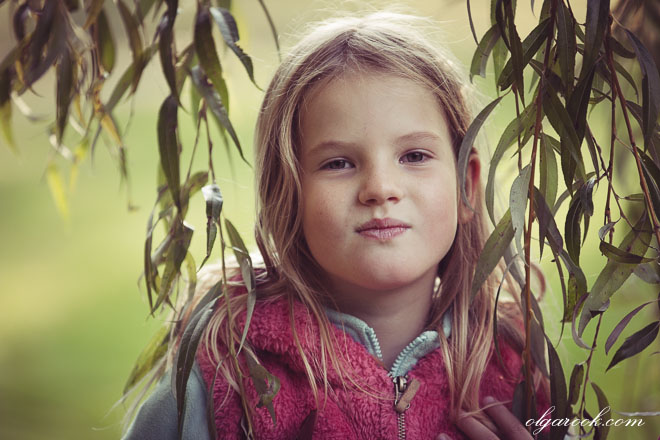 Portrait of a little girl next to a willow