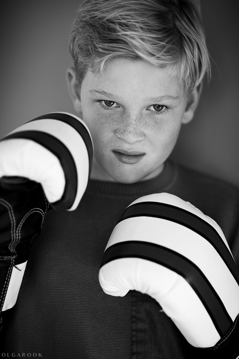 Black and white portrait of a boy wearing boxing gloves